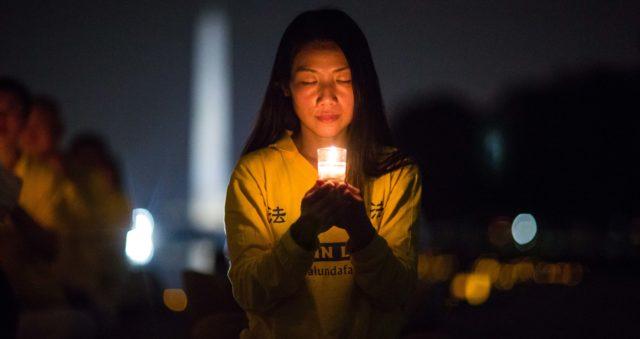 Kobieta dołącza do praktykujących Falun Gong podczas czuwania przy świecach przy Mauzoleum Lincolna w Waszyngtonie 20 lipca 2017 r., by uhonorować tych, którzy zostali zabici w trakcie prześladowań w Chinach, które chiński reżim rozpoczął 20 lipca 1999 r. (Benjamin Chasteen)