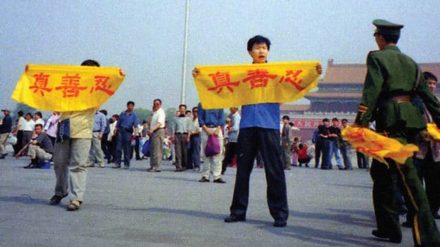 """A Chinese policeman (right) approaches Falun Gong practitioners on Tiananmen Square as they hold a banner that reads """"Truthfulness Compassion Forbearance"""""""