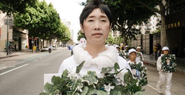 <b>Pani Wang Yifei </b> trzyma wieniec żałobny opłakując swoją siostrę, która została zabita w chińskim obozie pracy, ponieważ stanęła w obronie swojej wiary w Falun Gong. Pani Wang uciekła z Chin, aby uniknąć tego samego losu i jest tutaj pokazana w marszu w Los Angeles w 2016 roku.
